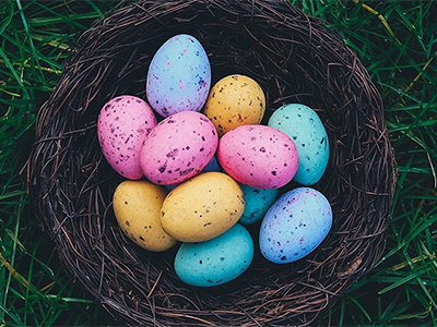 A photo displaying a basket full of pink, orange and blue Easter eggs