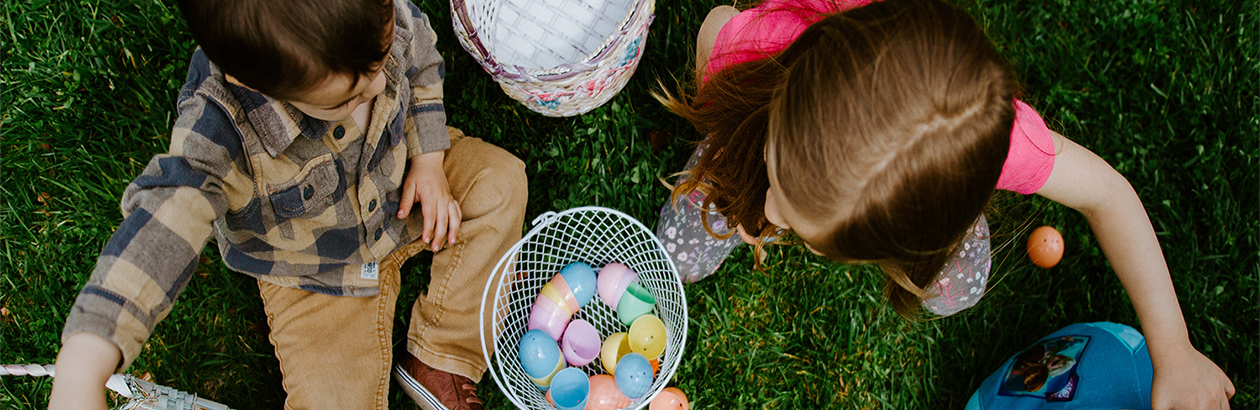a photo showing two children sitting on some grass playing with Easter eggs and baskets