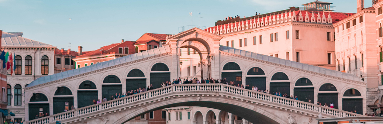 Photograph of tall buildings, a bridge across water with people standing on it and blue sky in Venice