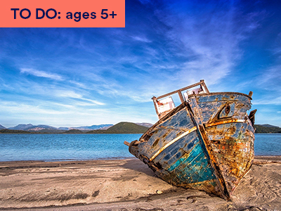 Photograph of washed up ship on sandy beach, blue sky and mountains. Keywords: TO DO: ages 5+