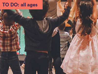 Photograph of children following instructor for a dance. Children with arms raised. Keywords: TO DO: all ages