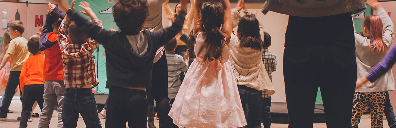 Photograph of a group of children facing a grown up and following instructions. All raising arms