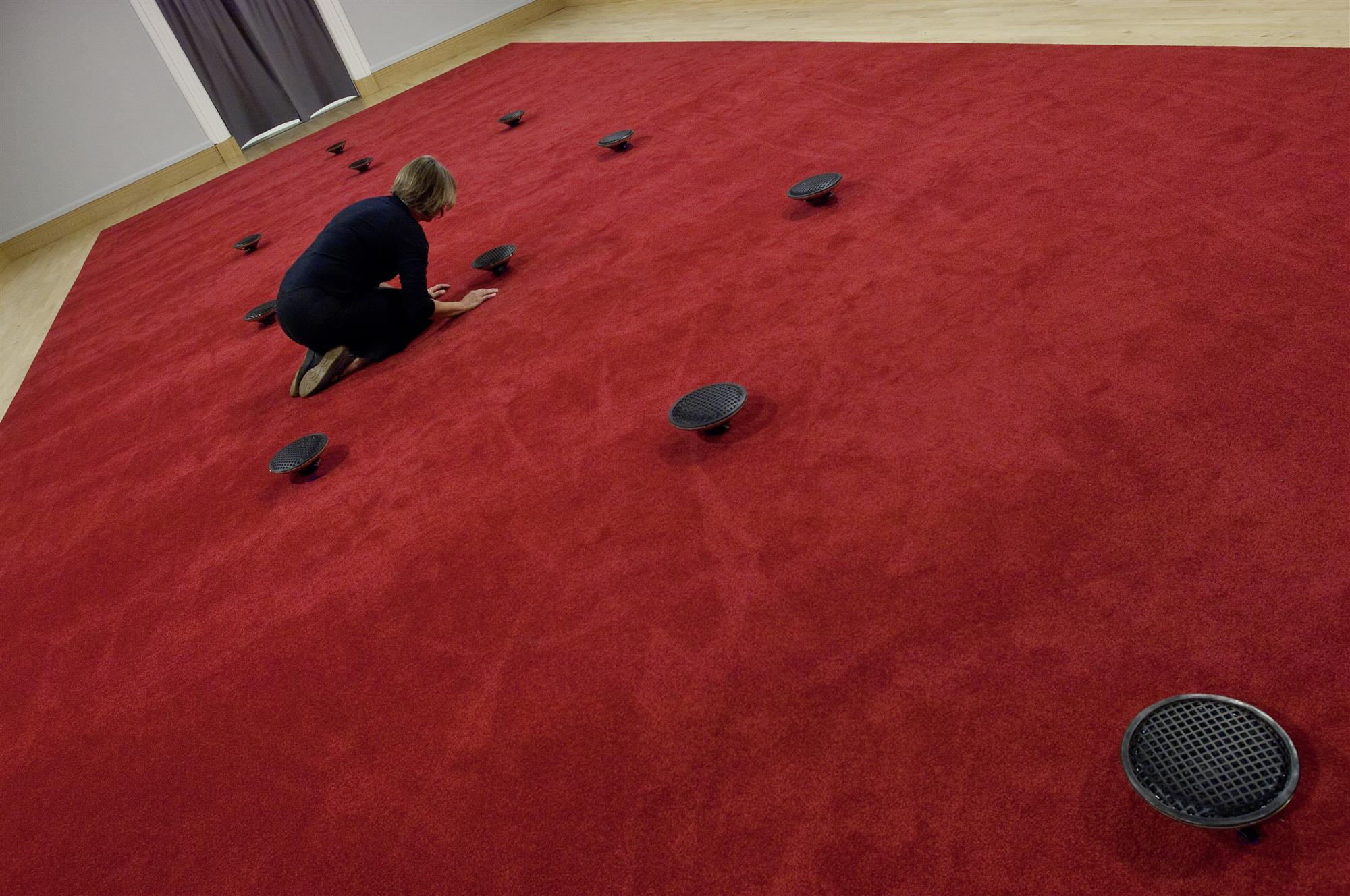 a photo of James Webb Prayer installatino in the Djanogly Gallery: a red carpet with 12 floor based speakers
