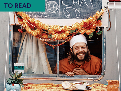 Man poking head out of food van with food on table in front Keywords: TO READ