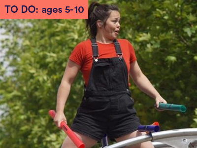 Female dancer wearing red top and black dungarees stands holding instruments. Keyword in the corner TO DO: ages 5-10