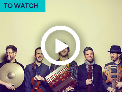 Photograph of MABON band members smiling and holding instruments. White play button overlay. Keyword in the corner TO WATCH