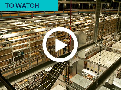 Photo of the University of Nottingham archives. Many rows of shelves stacked with brown paper files with play button. Keywords: TO WATCH