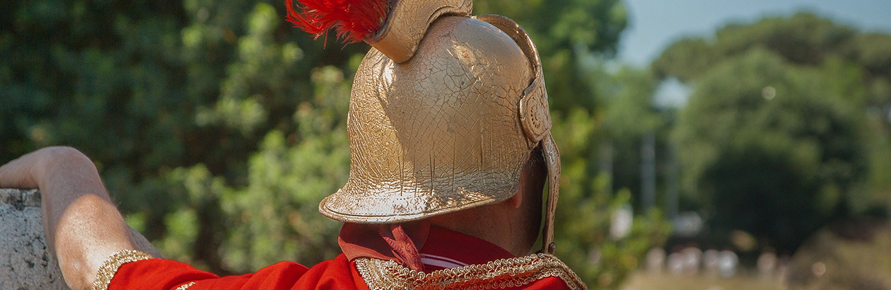 Photograph of the back of the man dressed as a Roman soldier with red cape and gold helmet with red feathers