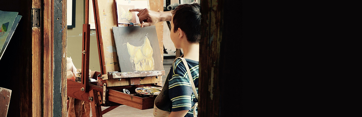 Photograph of a boy in a classroom in front of a painting easel learning