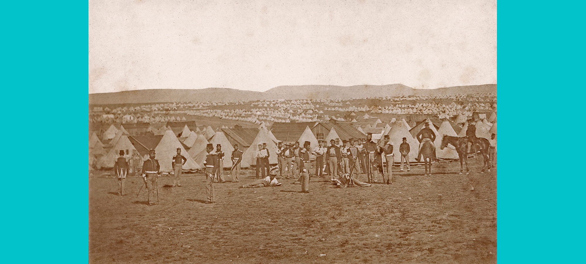 photograph taken of men at a camp standing in soldier uniform in front of tents