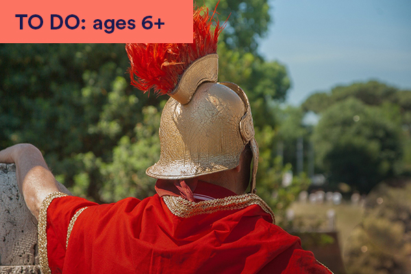 Photo of the back of a man dressed as a roman soldier wearing gold armour and helmet with red feathers. Keywords in corner: TO DO: ages 6+