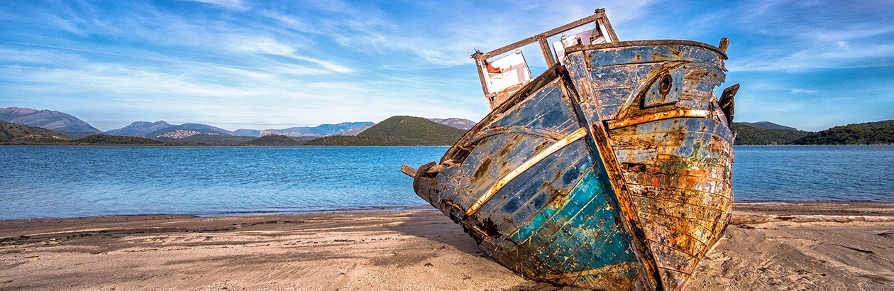 Photograph of ship washed up on sands with mountains and sea in the background