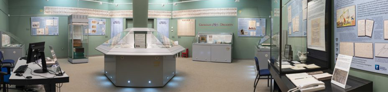 Panorama image of inside Lakeside's Weston Gallery. Image, cabinets and posters on surrounding walls with central exhibition stand.