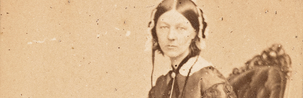 Photograph of seated Florence Nightingale on brown background