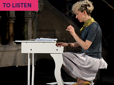 Photograph of Xenia Pestova Bennett playing miniature piano with grey top and green scarf. Keywords in corner: TO LISTEN