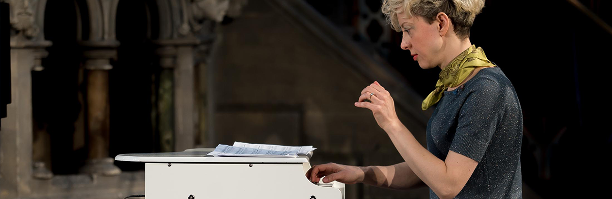 Photo of Xenia Pestova Bennet playing a miniature white piano wearing a grey top and green scarf