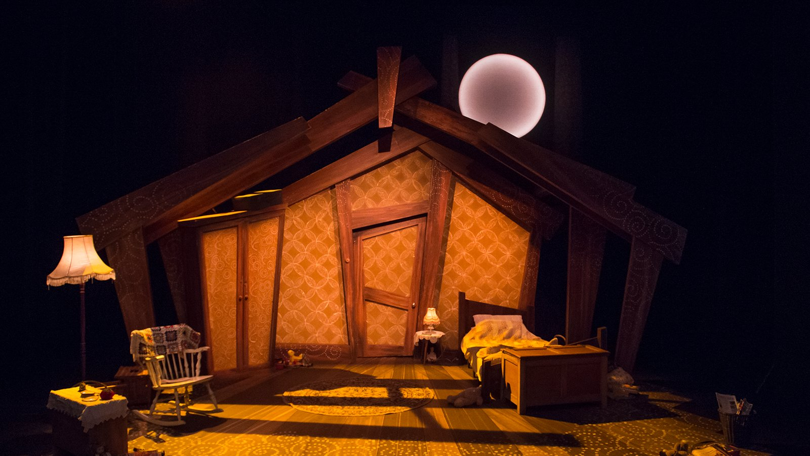 Photo of set design of Little Red Riding Hood, with a cozy home's interior, with bed, rocking char, wardrobe and floor lamp