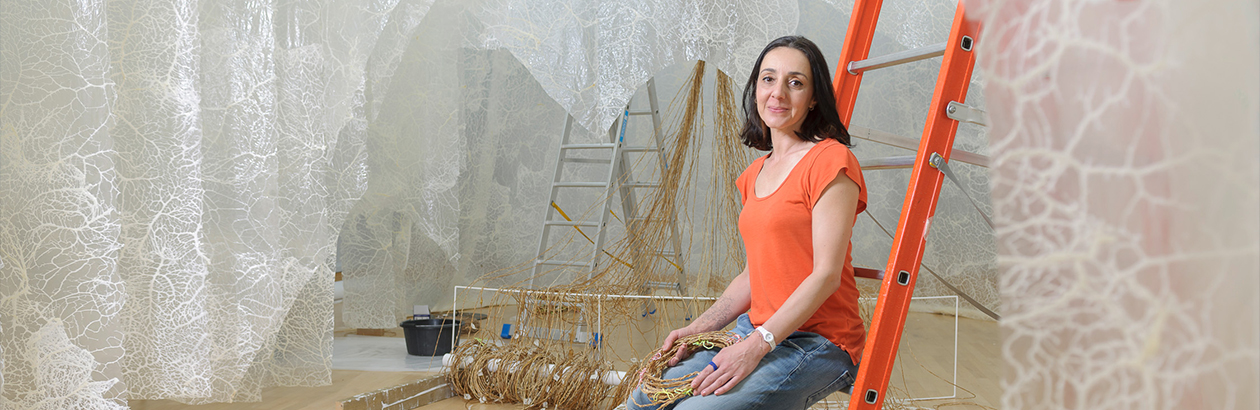 Elpida Hadzi-Vasileva sitting while the installation of her work Fragility in the Making Beauty exhibition, Djanogly Gallery, 2016