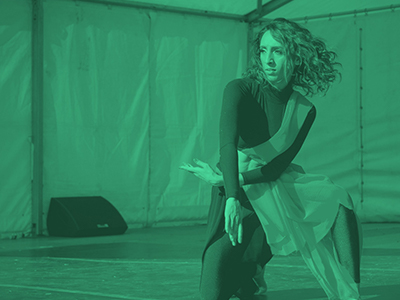 Photograph of woman dancing on stage with green colour opaque overlay