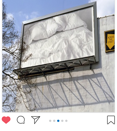 Photograph of billboard of an empty bed by Felix Gonzalez-Torres