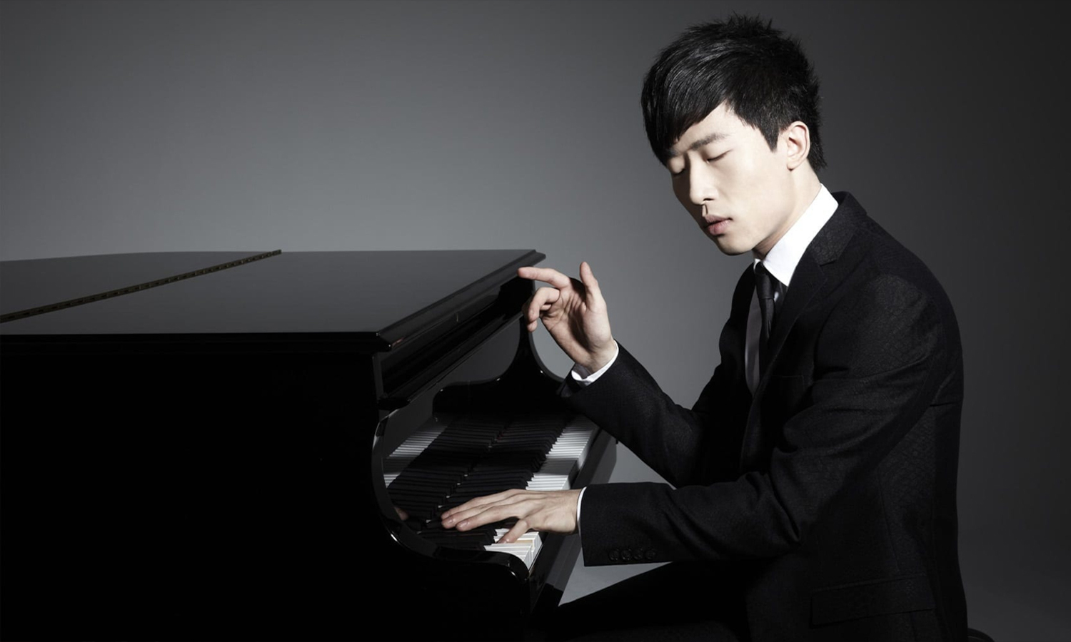 Ji Liu performing at the piano with a grey background