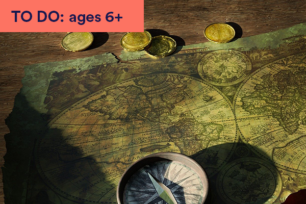 Photograph of old map on table with compass and gold coins. Keywords in corner: TO DO: ages 6+