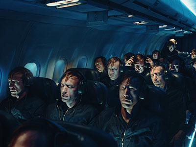 People on a plane in darkness wearing headphones