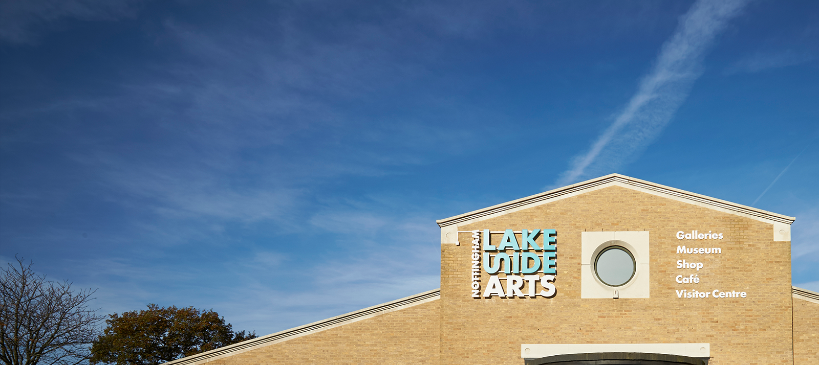 Lakeside building with logo against blue sky