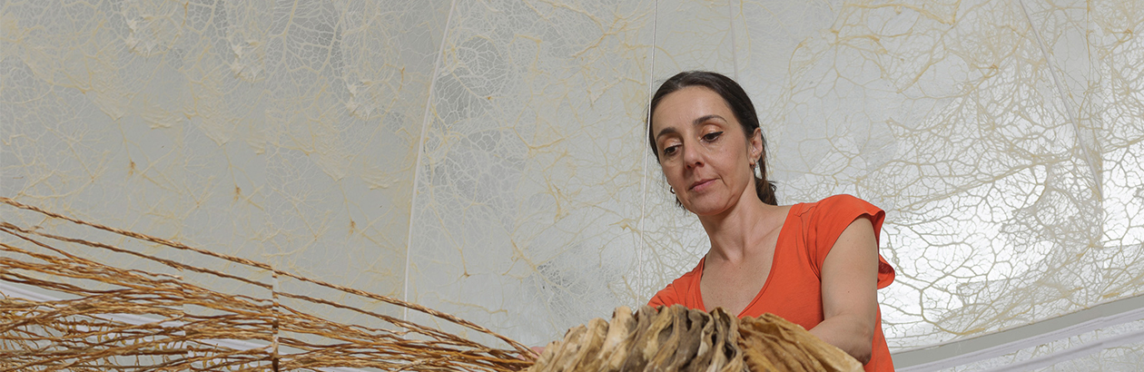 Photograph of Elpida Hadzi-Vasileva on a ladder looking over a brown knotted artwork