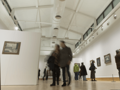 Visitors enjoy the Lowry exhibition in the Djanogly Gallery