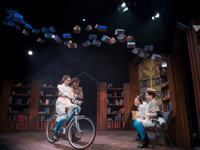 Girl on bicycle in Blue Stockings in the Djanogly Theatre